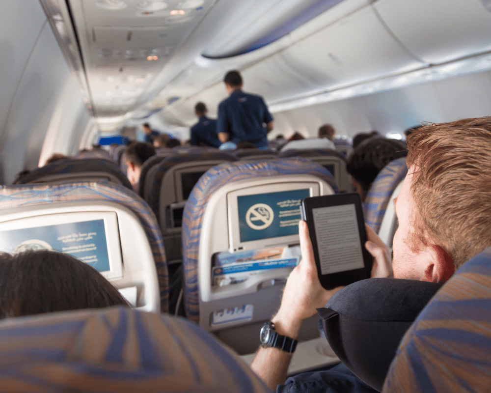 飛行機の中でKindle電子書籍リーダーを読んでいる人